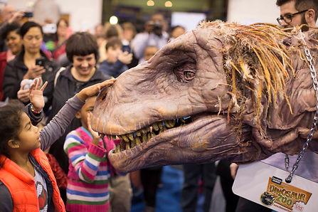 Child admiring a dinosaur at the ChiTAG Fair