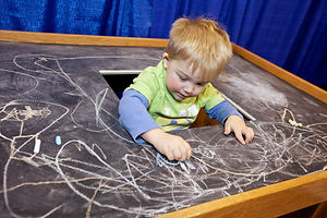 Child playing with chalk at fair