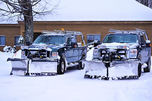 Two parked snowplow trucks backed in to