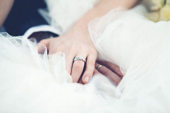 Bride and groom showing their wedding rings.