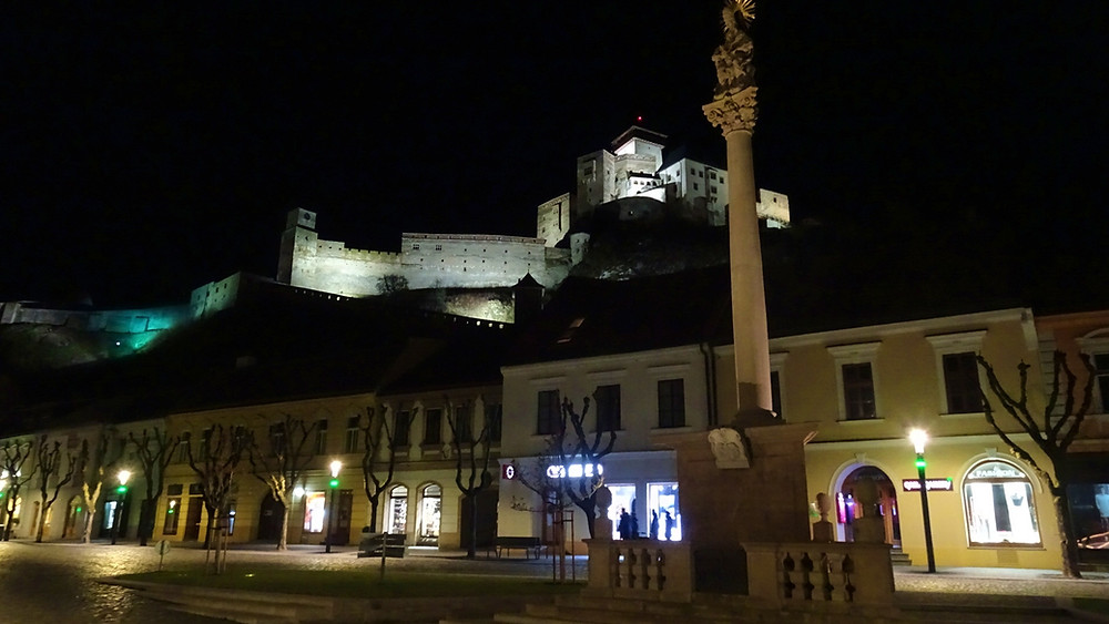 Trencin Castle by night - with Plague Column in foreground