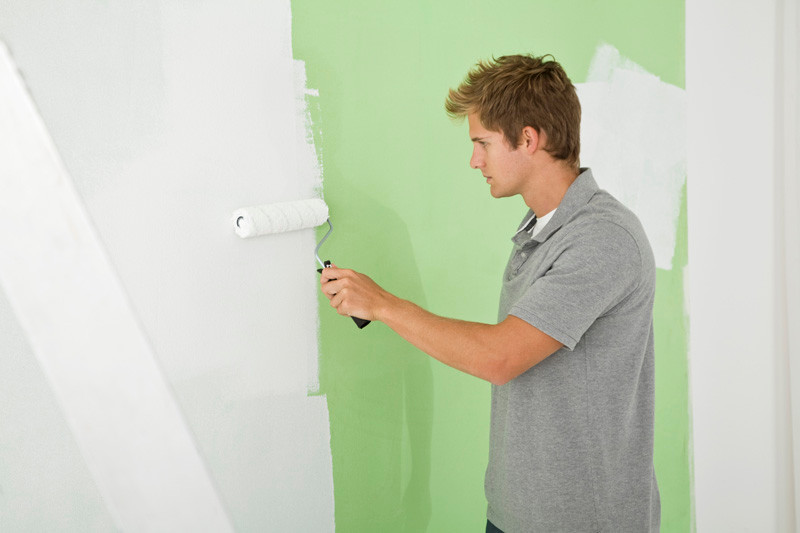 man painting wall white in co-op