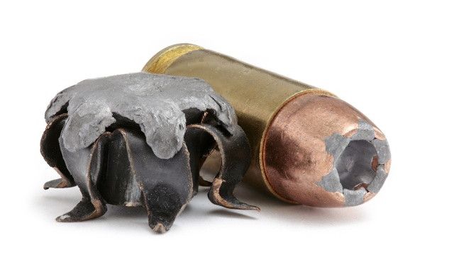 A hollow point cartridge, and a fired hollow point bullet after expansion