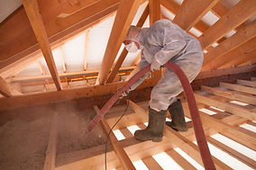 Worker with a hose is spraying ecowool insulation in the attic of a house. Insulation of t