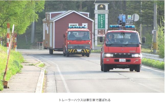 被災者の街にトレーラーハウスを運ぶ牽引車。再利用できる仮設住宅として注目されている。