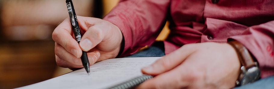 Auf dem Bild sieht man die Hände eines sitzenden Mannes. Die Linke hält einen Schreibblock während die Rechte etwas notiert.
