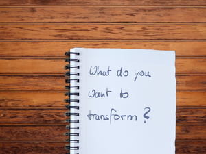 """The picture shows a notebook on a wooden table saying """"What do you want to transform?"""""""