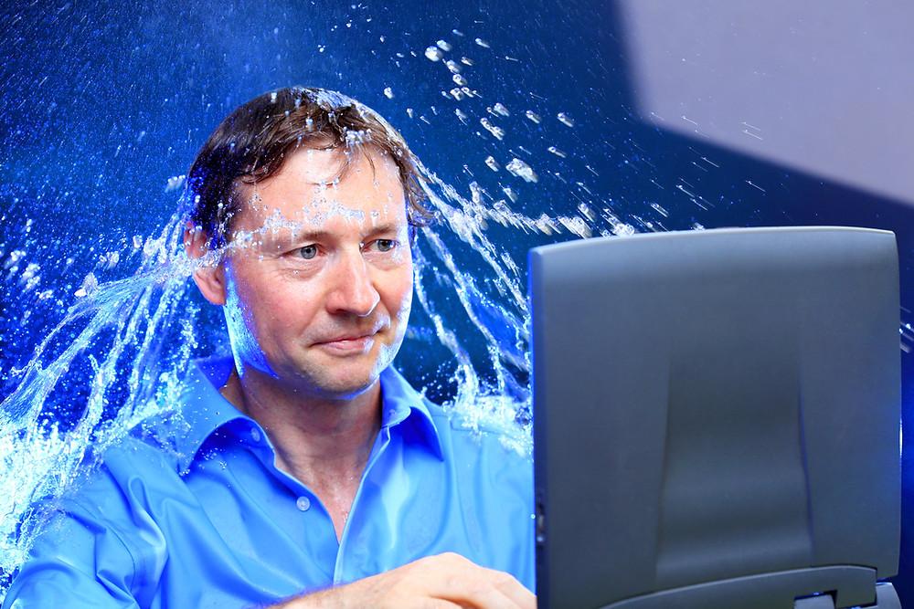 Artikel: Klarheit kommt manchmal erst nach einer kalten Dusche. Das Bild zeigt einen Mann, der vor einem Laptop sitzt und über dem gerade kaltes Wasser ausgeschüttet wird.