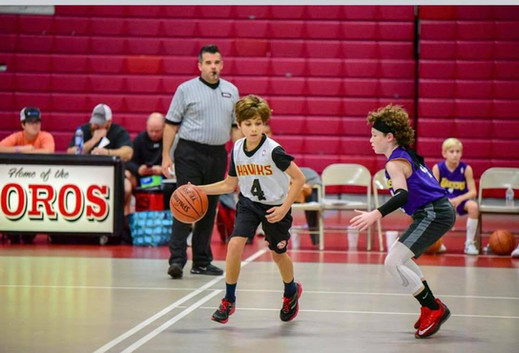 young basketball player dribbles near defender