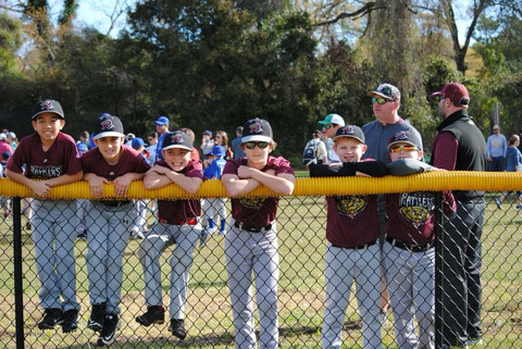 group of young baseball players lining the fence - very norman rockwell-esque