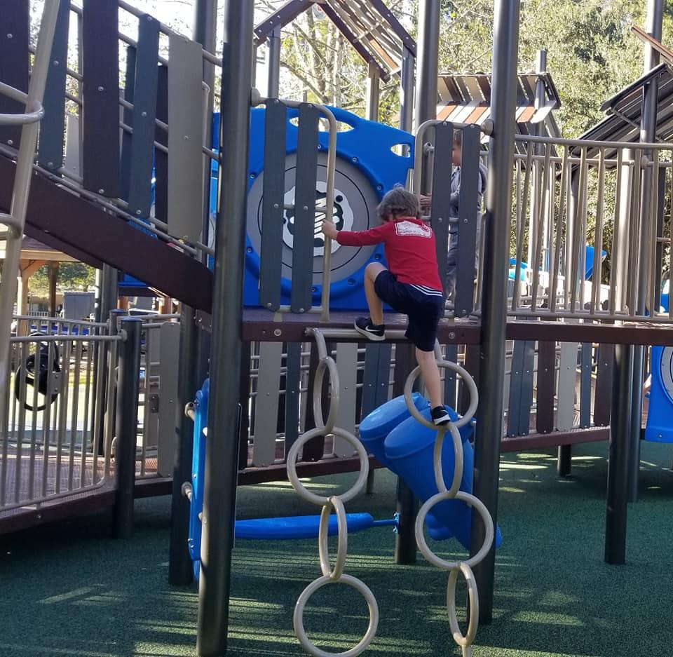 child climbing playground structure at kid's park