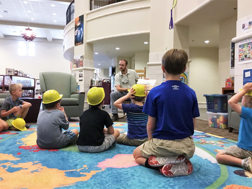 kids in hard hats listening during story time
