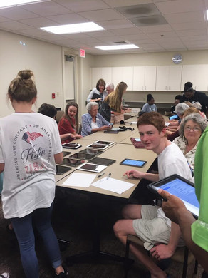 cyber seniors group meeting with local high school students to figure out how to use their tablets
