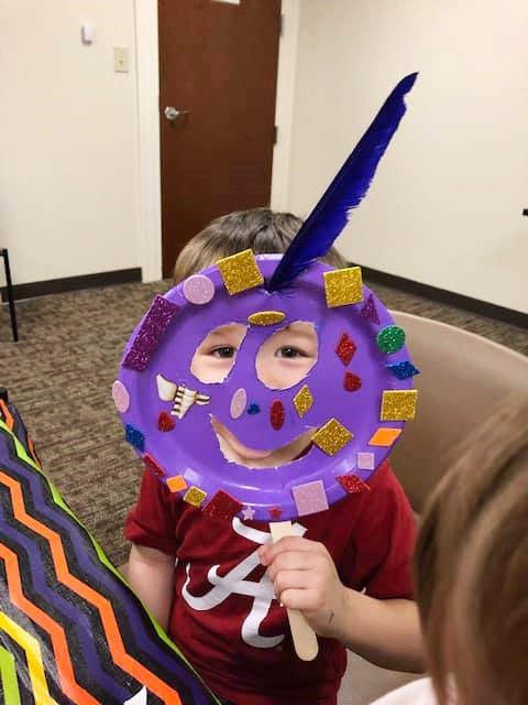 a little kid creates a mardi gras face mask at craft time