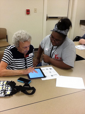 young woman helping an older woman with her tablet so that she can facetime her family