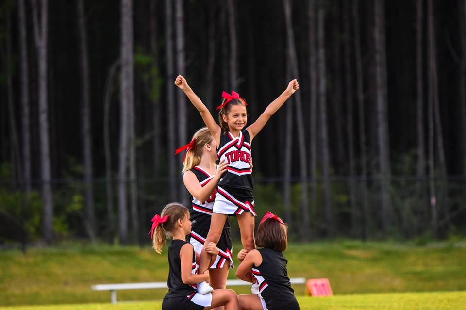 young cheerleaders cheering on their team