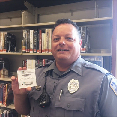 local spanish fort police officer showing off his new library card