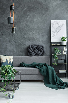 Dark green blanket on grey sofa against