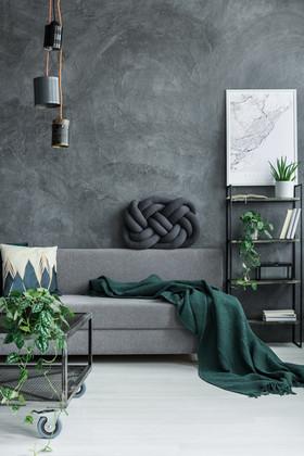 Dark green blanket on grey sofa against