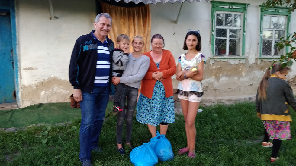 Pastor Vasily gives food to village family