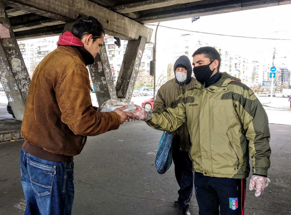 Giving out wrapped hot meals to people left jobless and homeless due to COVID-19