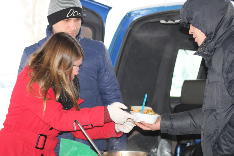 Faith Woods of MPI helps with giving out food during homeless feeding
