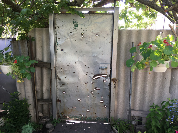Metal gate to a home in the East with bullet hole damage