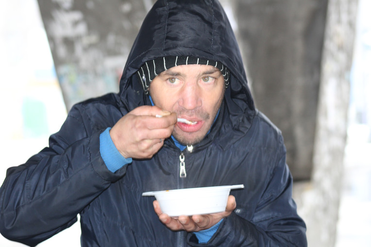 Consuming a hot meal freely distributed on the street