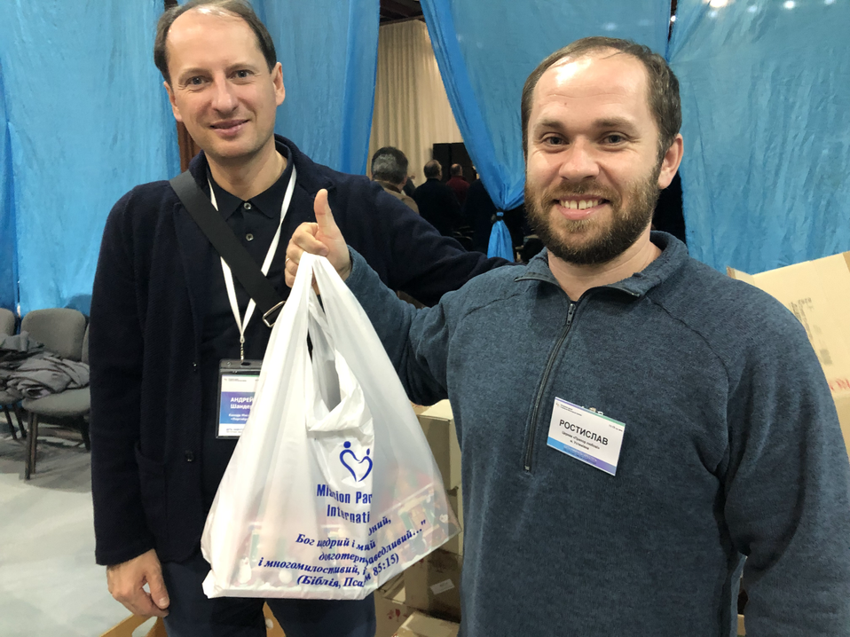 Pastor receives gifts for his children at MPI's annual Christmas conference in Kiev