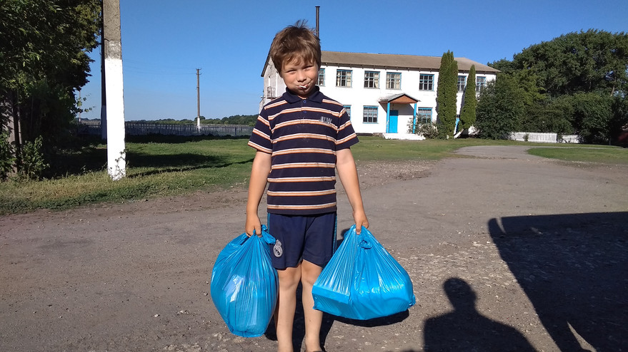 Village boy receives food bags for his family