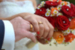 Bride and Groom holding hands wearing new wedding rings and holding red bouquet