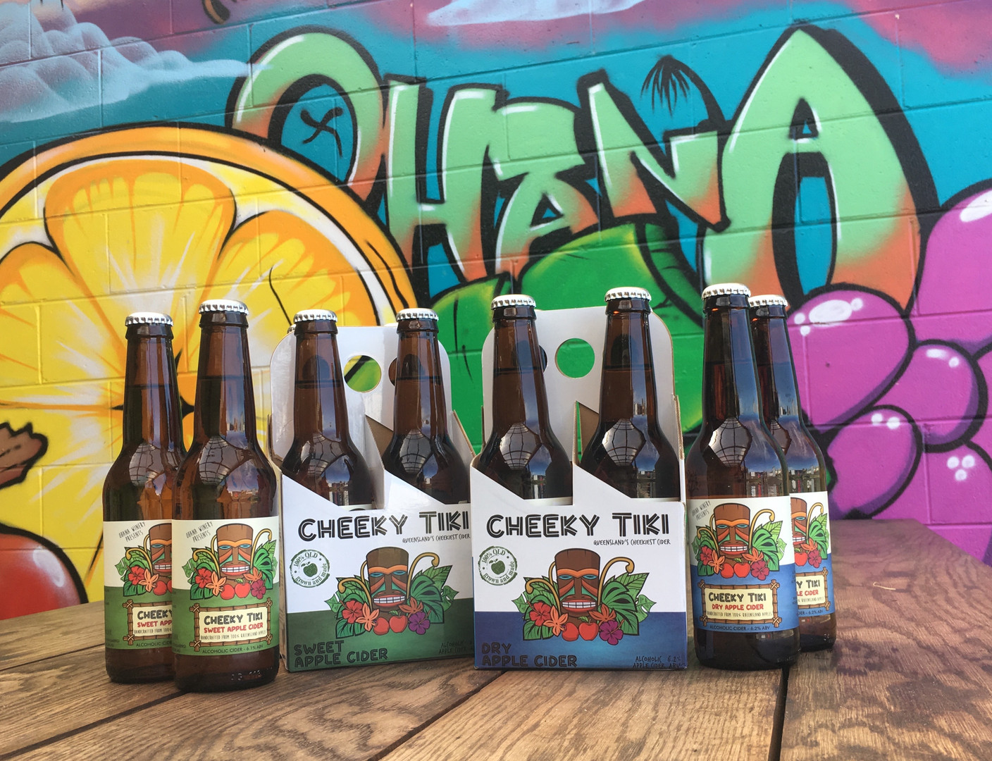 A group of cider bottles in four pack packaging on a brown table with a colourful mural grafitti background