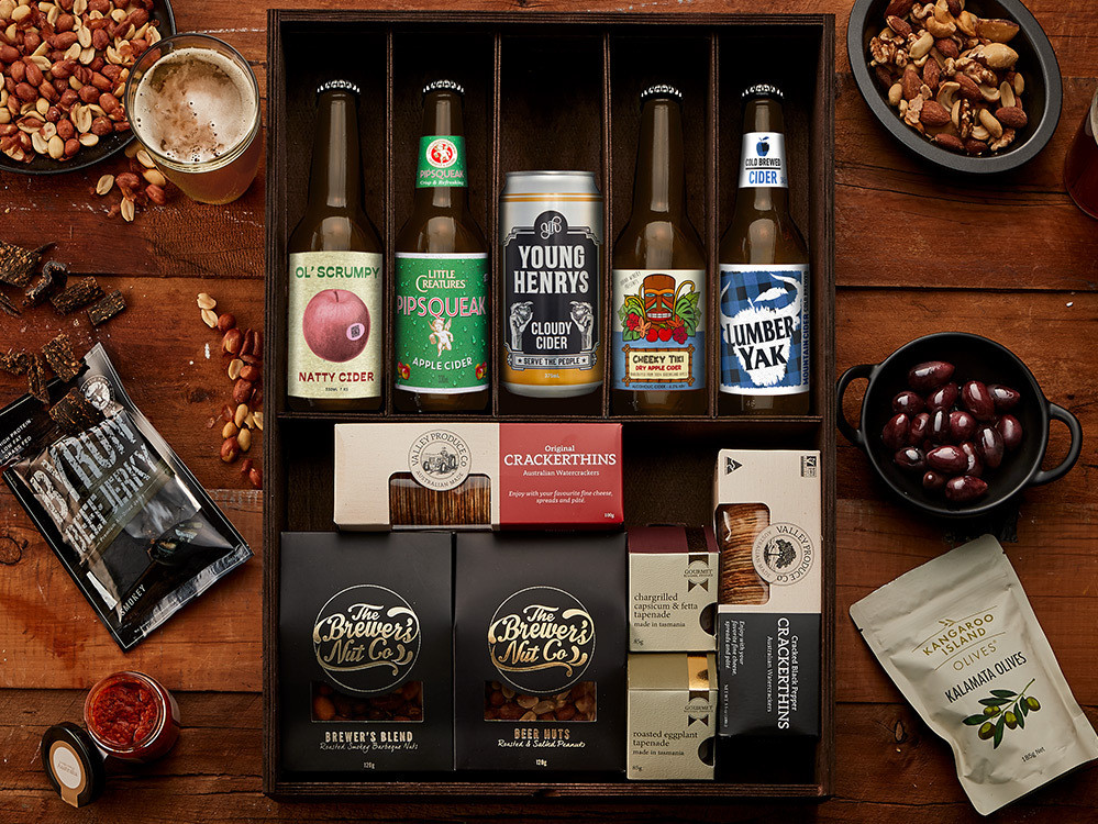 Flat lay image of five cider bottles in a nice gift box with nuts and crackers