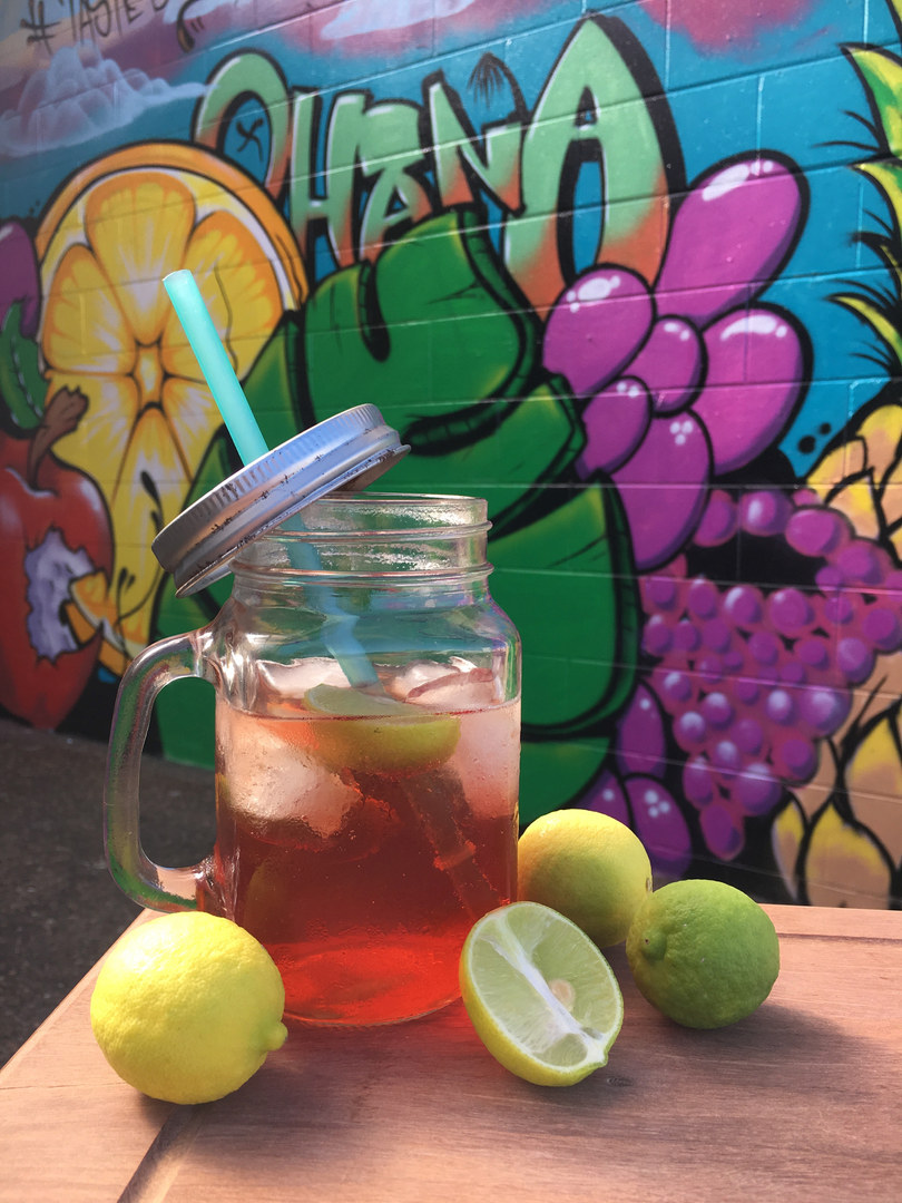 Pink - orange drink in a mug style glass with cut limes