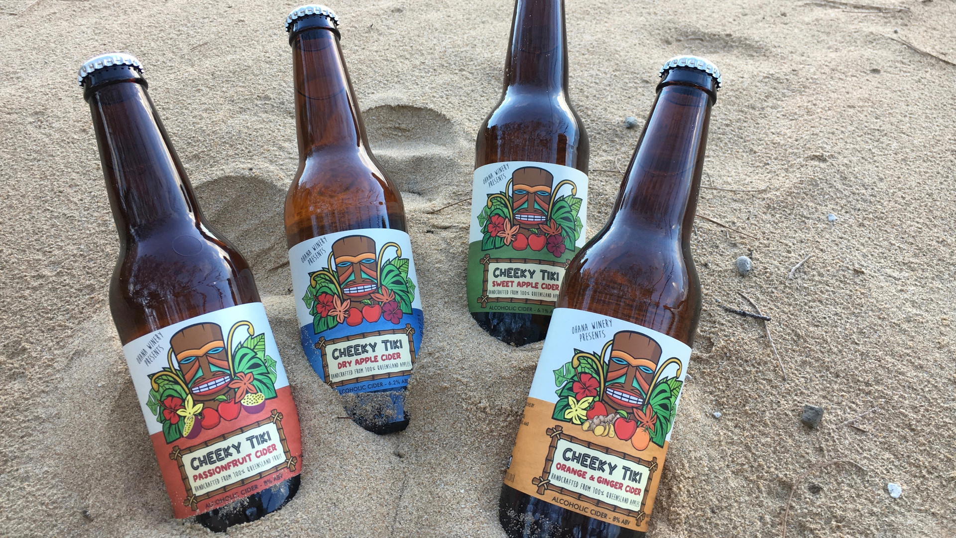 Four bottles of apple cider pushed into beach sand
