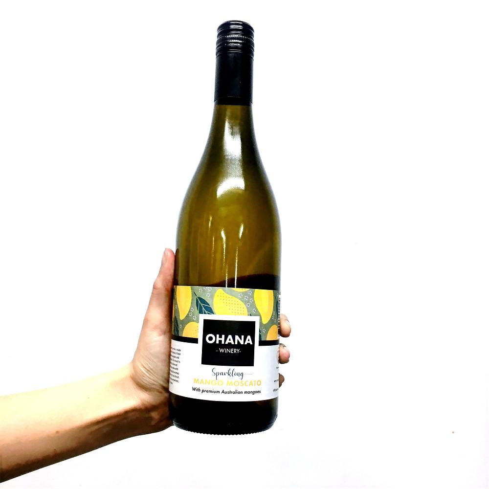 Hand holding bottle of mango wine