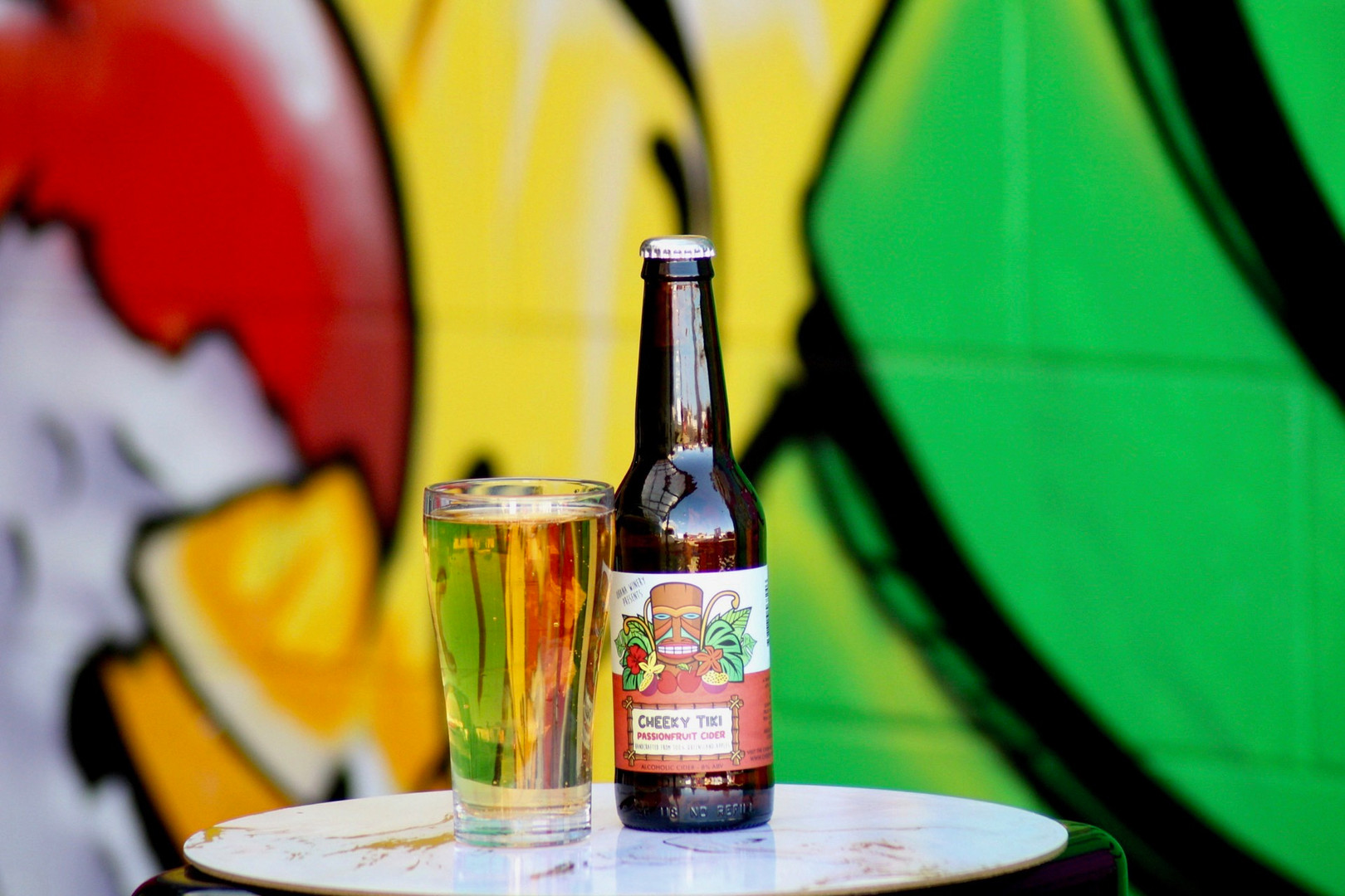 A bottle of passionfruit cider next to a glass of cider with colourful background