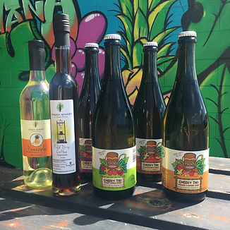 Bottles of cider and wine on a table with graffiti background