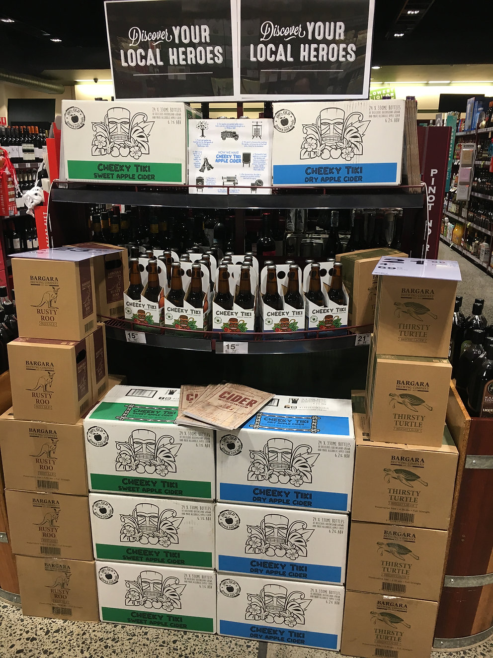 A shop display of apple cider and craft beer with lots of cardboard boxes and exposed bottles