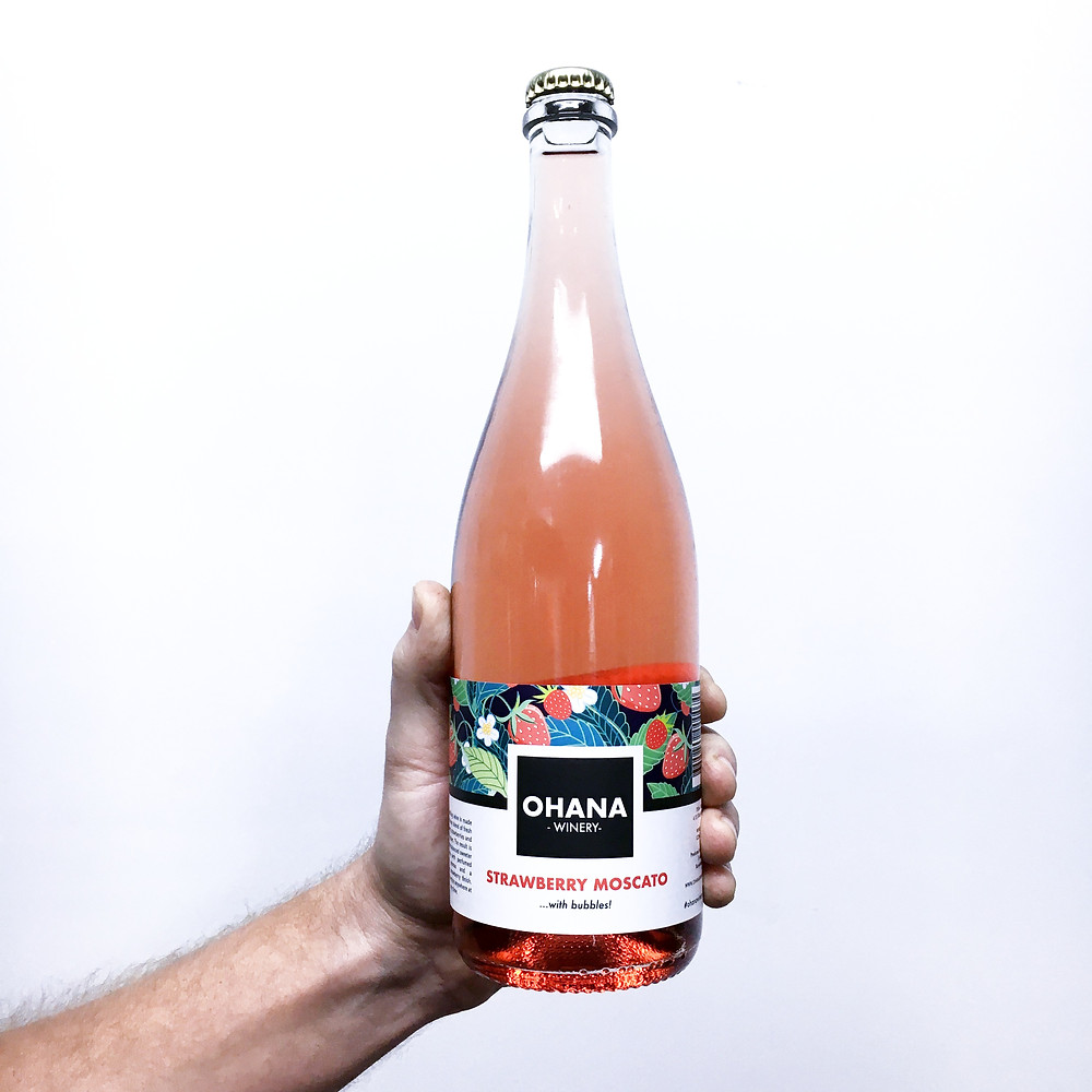 Hand holding bottle of pink strawberry moscato wine on a white background