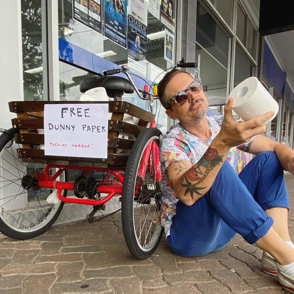 A tattooed man holding a roll of toilet paper in front of a red tricycle with a sign on it saying free dunny paper