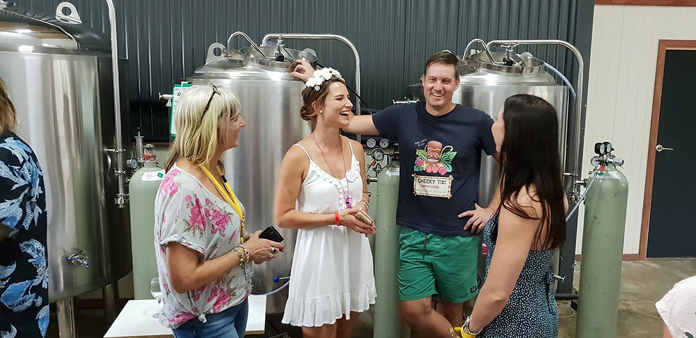 Girls smiling and man casually leaning against wine tank.