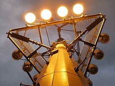 Telecommunications monopole with sports lighting installed