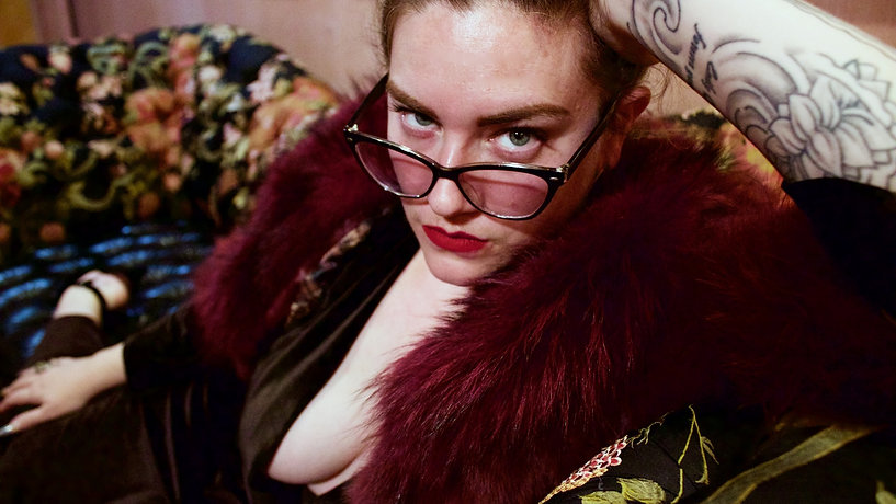 Dahlia Snow in fur and velvet, leaning on one arm, with glasses on nose starring with eye contact