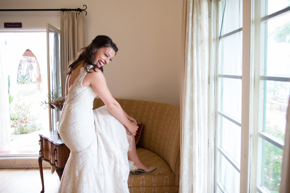 Beyond Happy Bride Putting Her Garter on before her Casa Romantica Wedding in San Clemente, California by Jen Marie Photography
