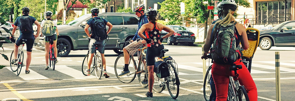 Photo of cyclists waiting at a stoplight in a cycletrack.