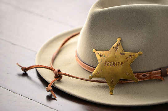 Cowboy hat with Sheriff badge on wooden