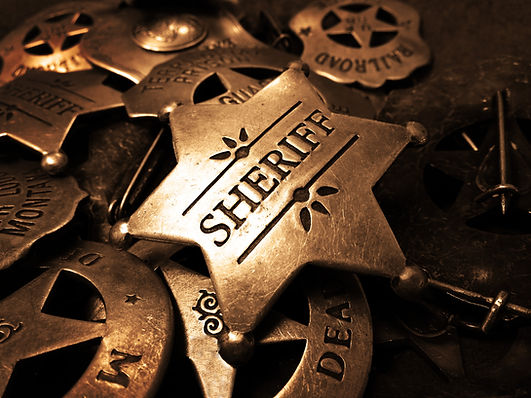 Sheriff's tin badge in pile of star law