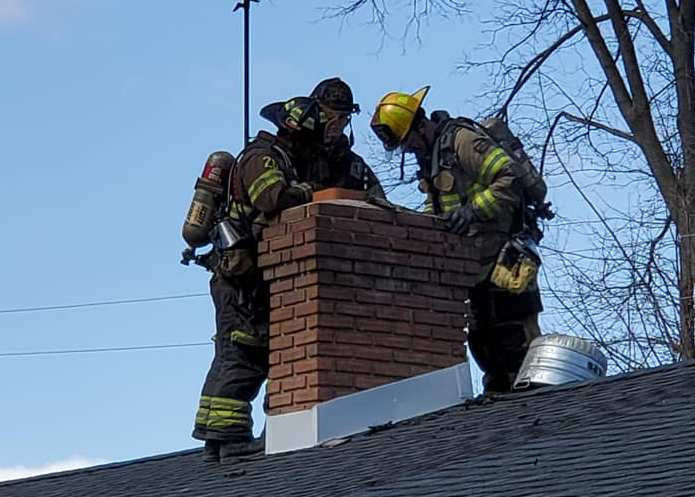 Firefighters inspect a chimney following a fire