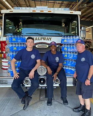 Firefighers sit on the front bumper of an engine next to several cases of donated waters.